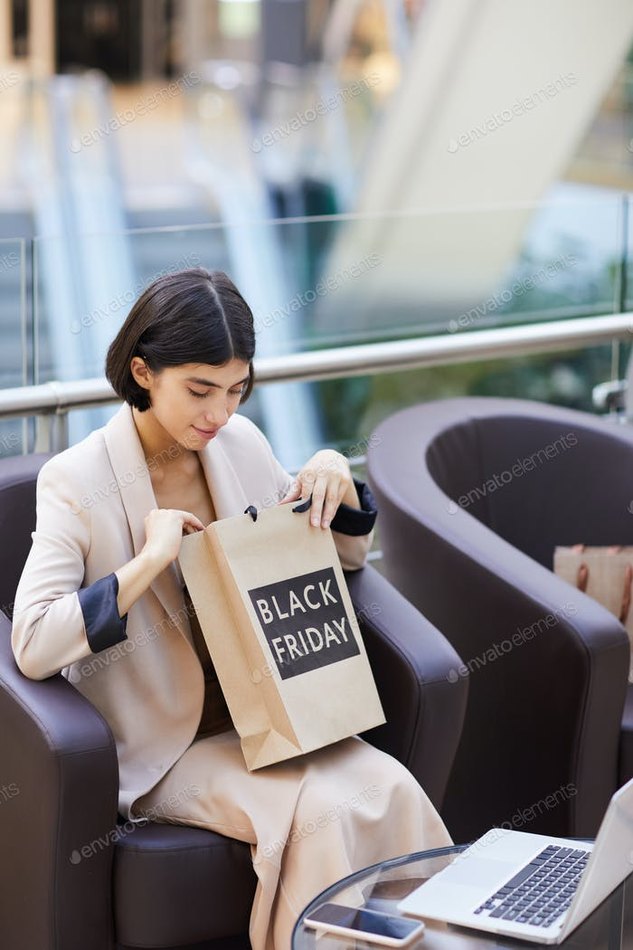 Beautiful Woman Looking into Shopping Bag