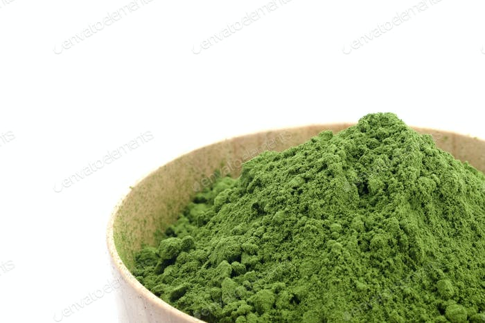 Green tea powder in woodbowl on white background.