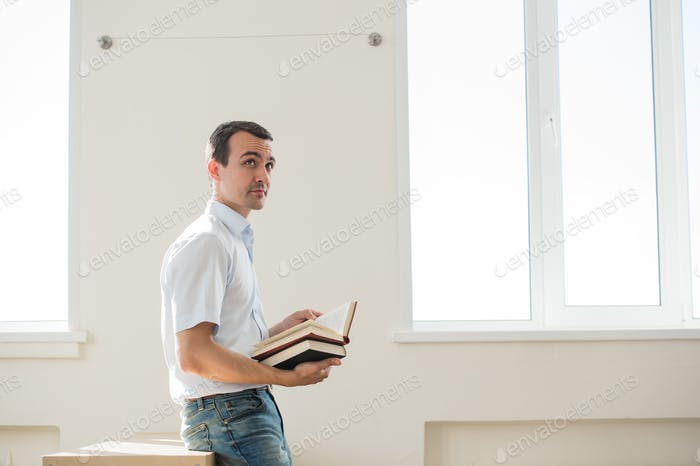 Thoughtful handsome pensive young man studying at class or living room, reading a book