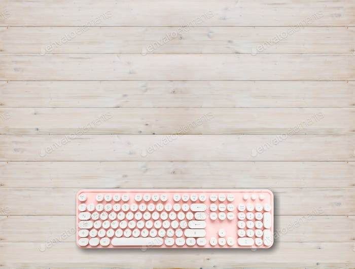 Computer keyboard pink color on wood background,