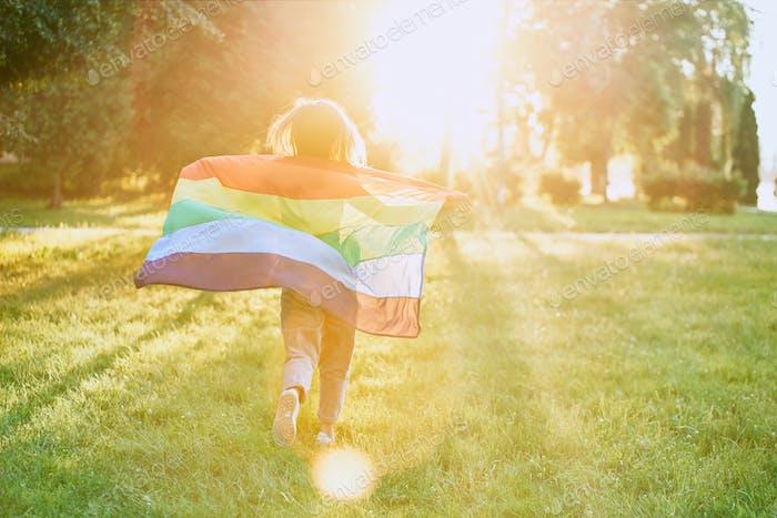 Girl running with rainbow lgbt flag behind back