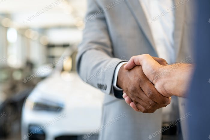 Car salesman and client handshake