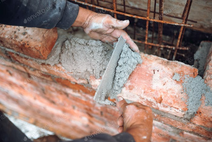 Bricklayer using trowel and hands for building exterior brick walls