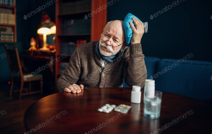 Sick elderly man puts ice on his head, headache