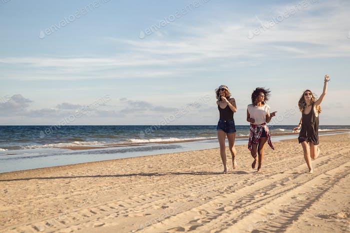 Gruppe von drei schönen jungen Frauen zu Fuß am Strand