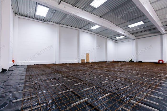 Floor concrete reinforcement at warehouse construction site.