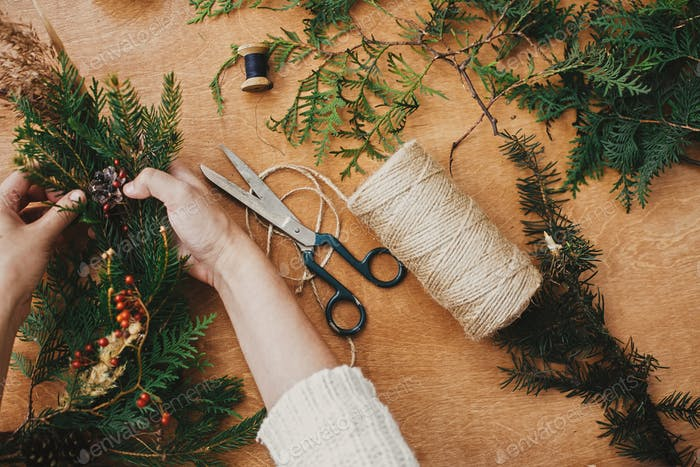 Hands holding fir branches, pine cones, berries, thread, scissors on wooden table, flat lay