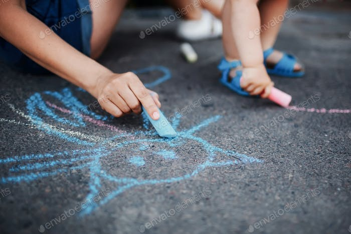 Close up of little girl drawing with chalks on the sidewalk
