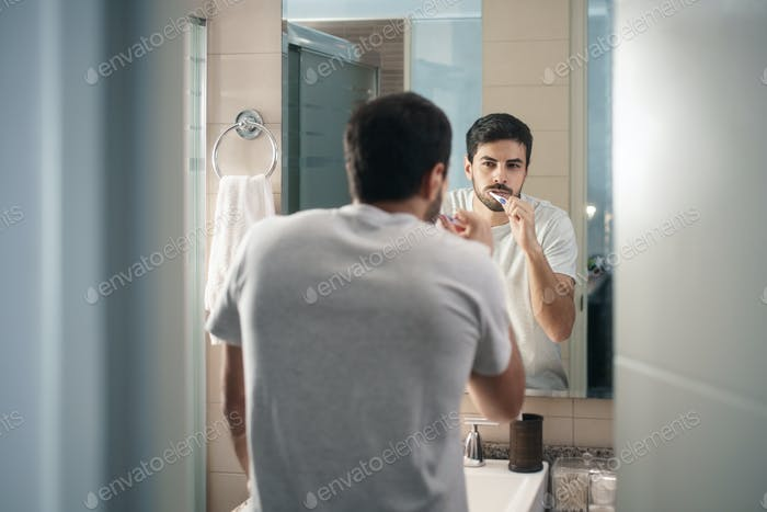 Hispanic Man Brushing Teeth In Bathroom At Morning