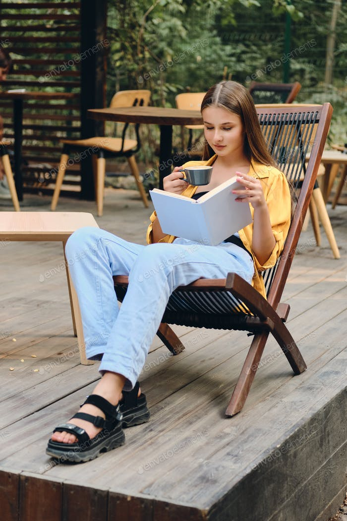 Beautiful brown haired teenage girl in yellow shirt reading book drinking coffee in city park