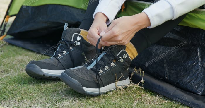 Woman wear sport shoes at camping site