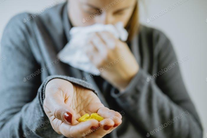 Frau reicht mit Pillen und einem Taschentuch. Kaltes Konzept