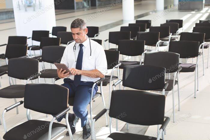 Male doctor sitting on chair and using digital tablet in conference room