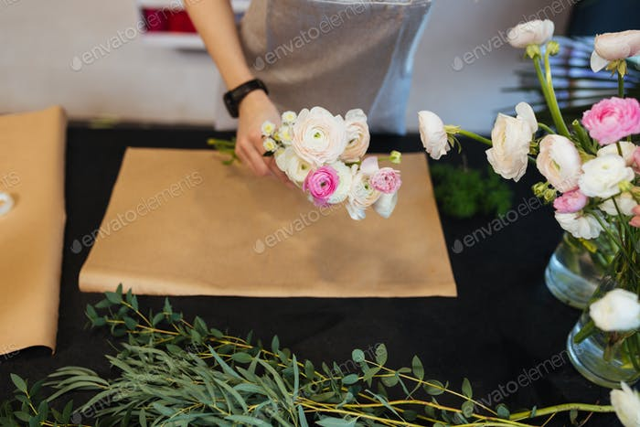 Hands of female florist creating bouquet on black table