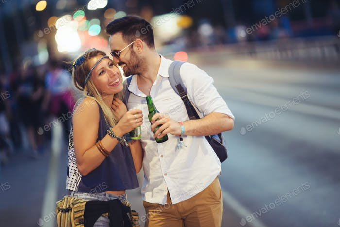 Couple drinking alcohol at night before festival