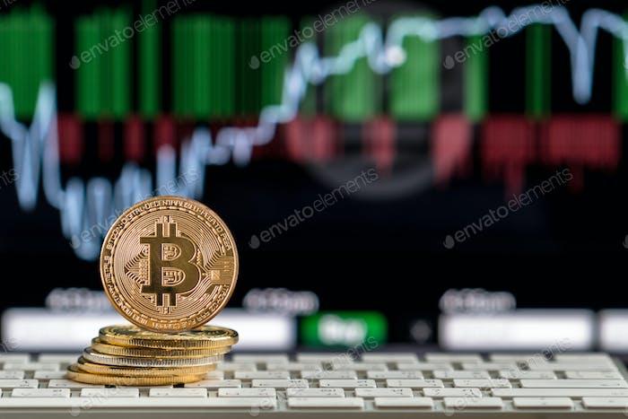 Primer plano de Bitcoins maqueta en el teclado sobre el gráfico de comercio de criptomonedas