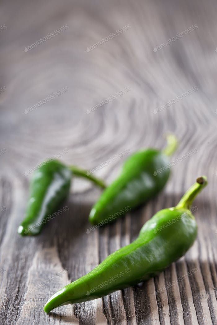 Three green hot peppers on a wooden table