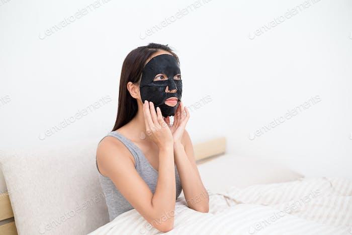 Женщина, использующая черную листовую бумажную маску