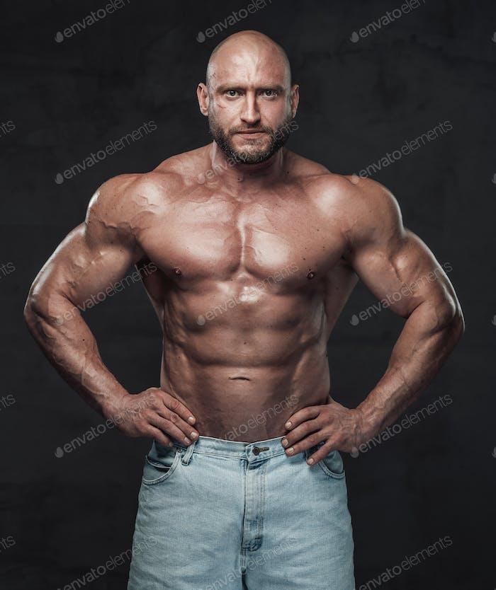 Handsome caucasian bodybuilder posing in dark background