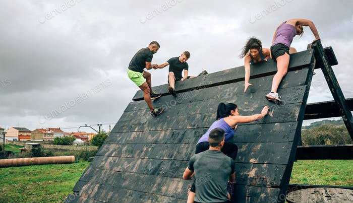 Participants in obstacle course climbing pyramid obstacle