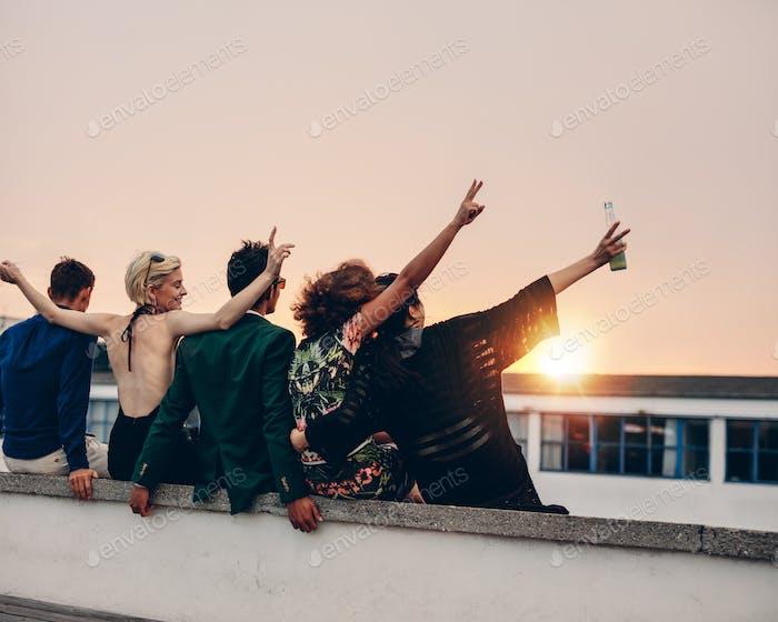 Junge Leute feiern auf der Terrasse mit Getränken