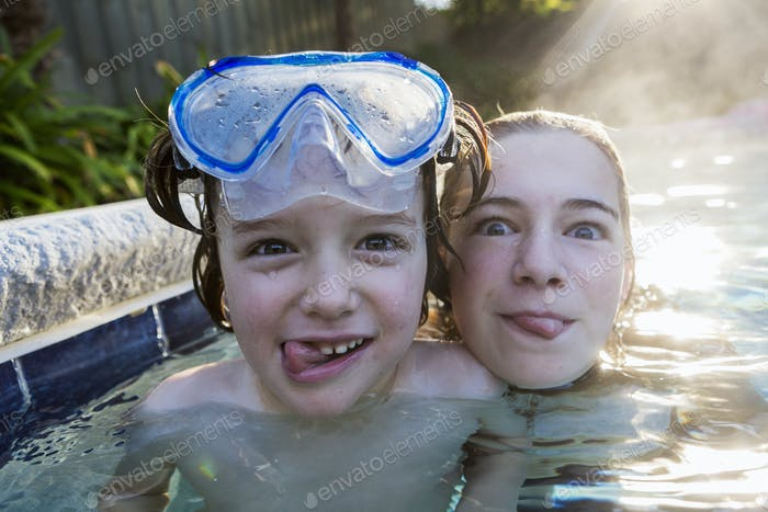 A teenage girl and brother in a warm pool, looking at the camera, sticking their tongues out.