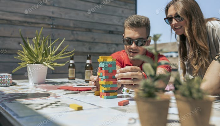 Man and woman playing with tower wooden stacking on terrace