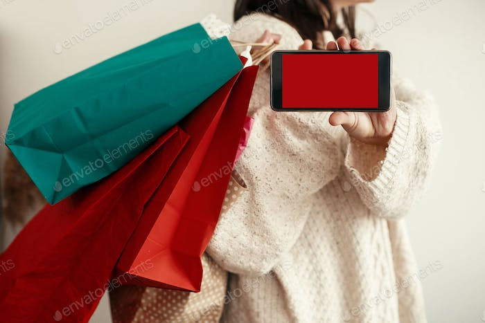 Happy Girl holding phone with empty screen and carrying colorful shopping bags
