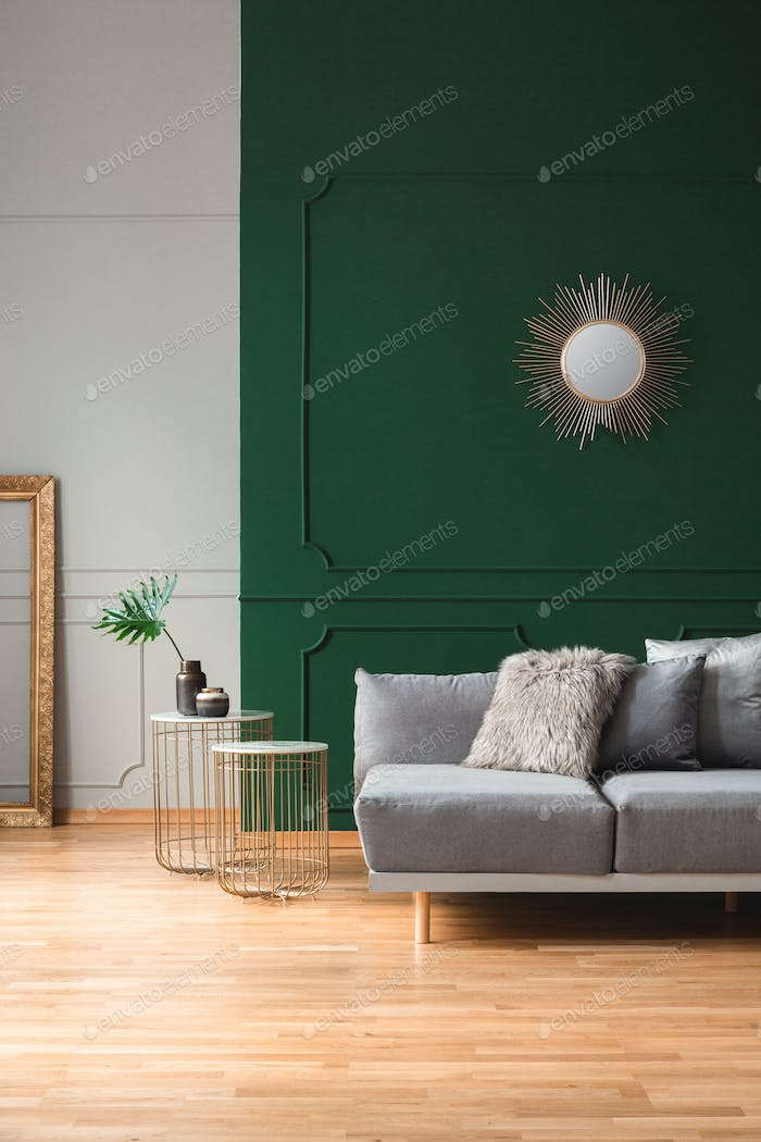 Sun shape mirror on empty green wall in stylish living room interior
