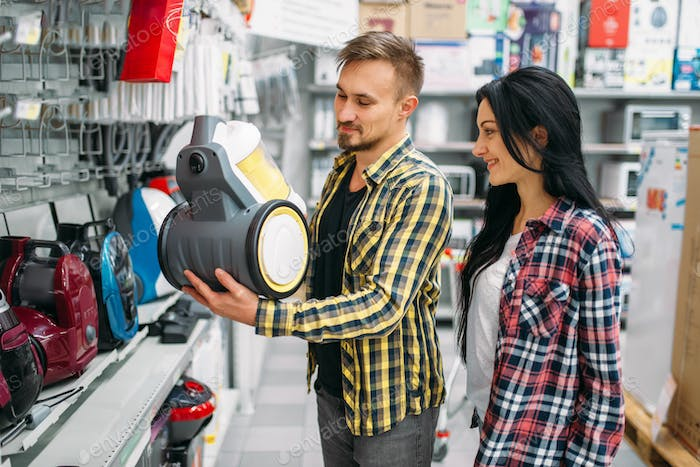 Couple choosing vacuum cleaner in supermarket