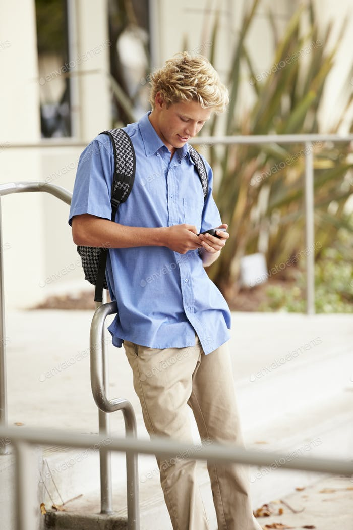 high school student stehend außerhalb gebäude mit telefon