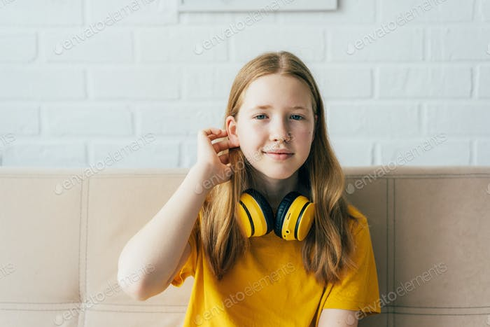 Portrait of a cute redhead schoolgirl in a yellow T-shirt with wireless headphones.