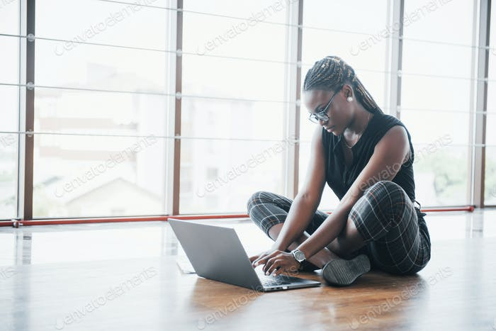 A young African American woman is happy with a laptop computer