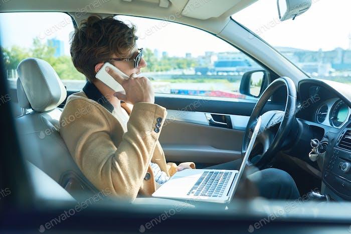Reicher Geschäftsmann, der per Telefon im Auto spricht