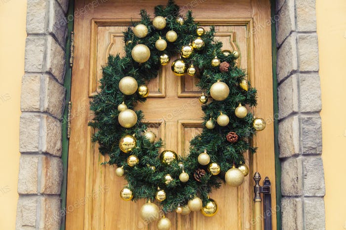 Christmas wreath with baubles and cones on a door.