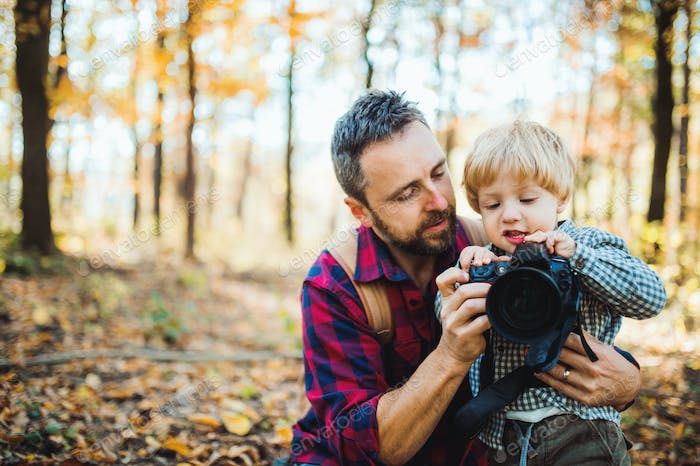 A mature father and a toddler son in an autumn forest, taking pictures with a camera.