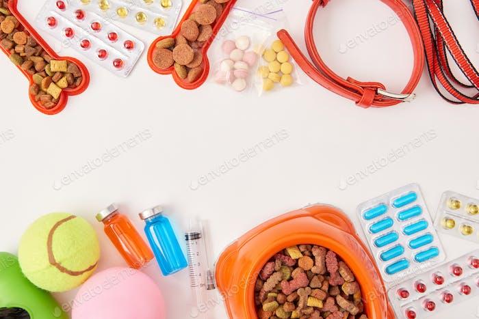 Collar plano con collar de perro, varias píldoras, bolas y cuenco con comida para perros en superficie blanca