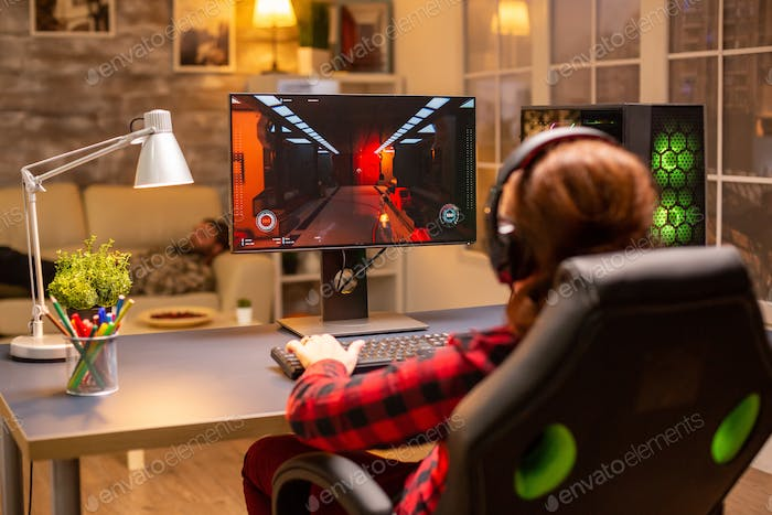 Back view of female gamer playing on powerful computer PC late at night in the living room