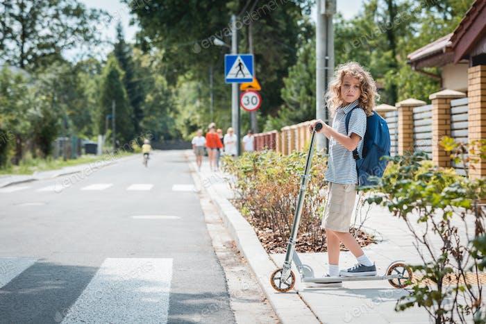 Niedlicher Junge mit Rucksack und Roller steht vor einem Fußgängerübergang auf der Straße