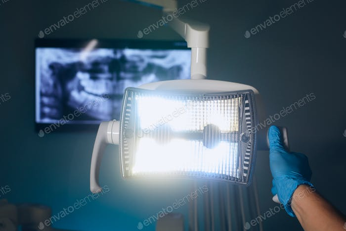 Dentist adjusting lamp against x-ray