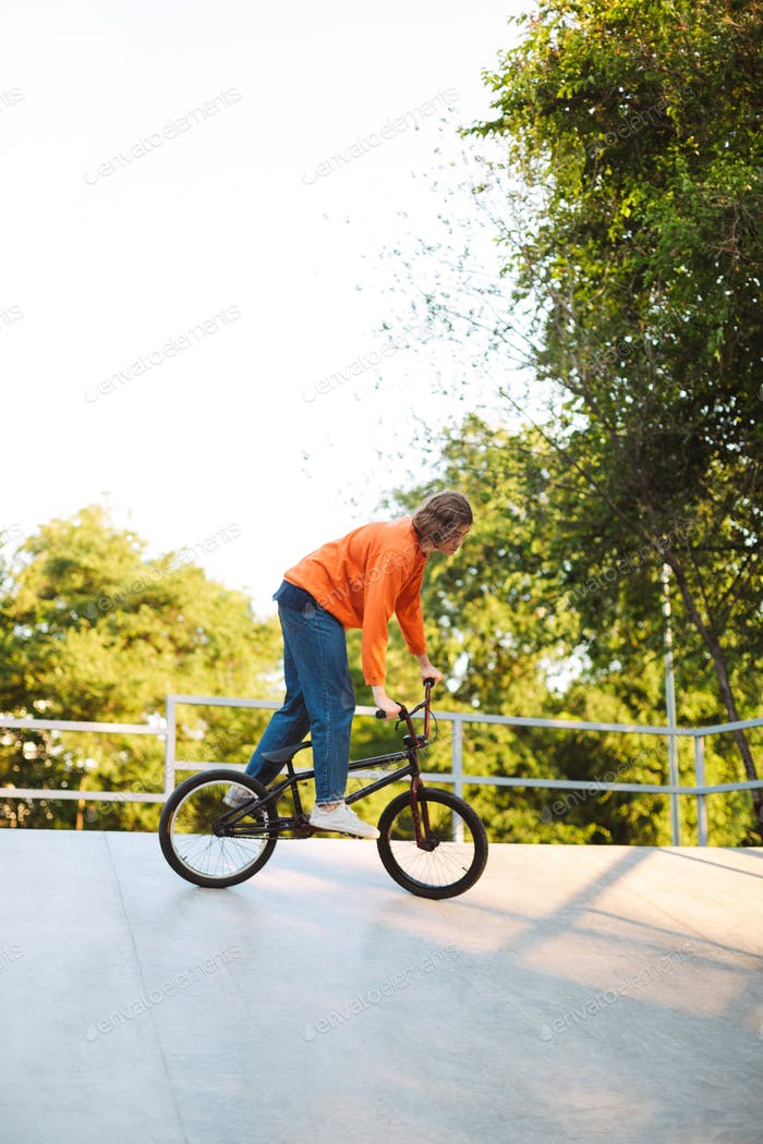 Cool young guy in orange pullover riding bicycle and practicing