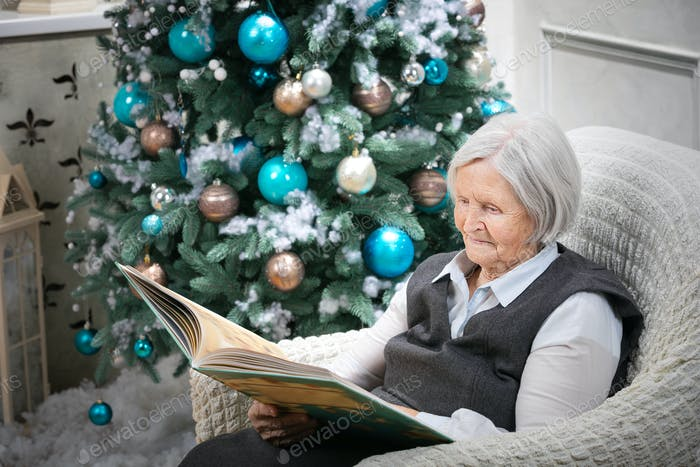 Senior woman reading a book beside a Christmas tree