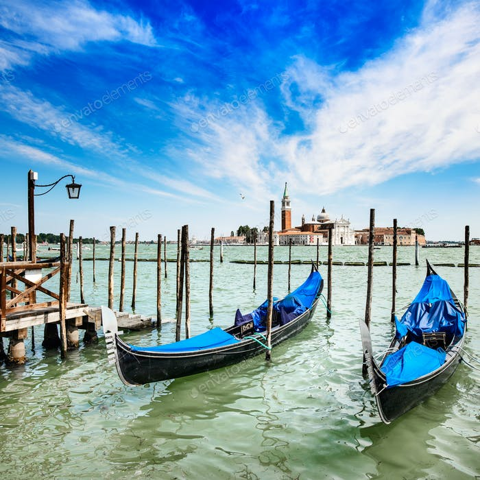 Venice, gondolas or gondole and church on background. Italy