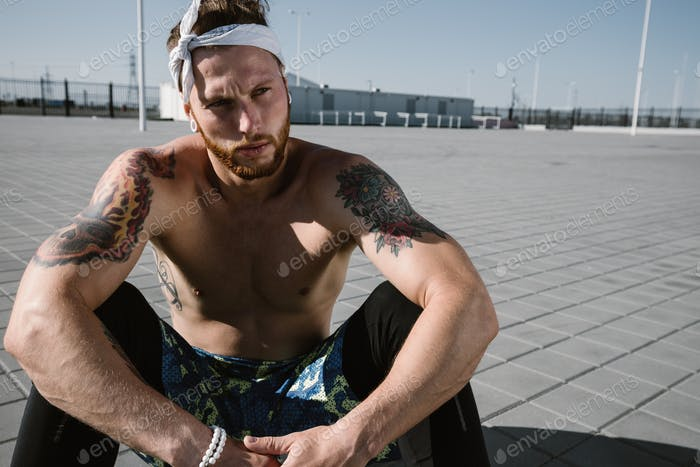 Young athletic man with a naked torso with headband and tattoos dressed in the black leggings and