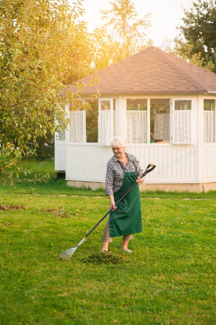 Lady with rake in garden