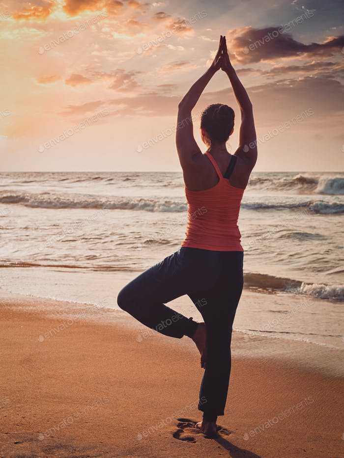Young sporty fit woman doing yoga tree asana on beach