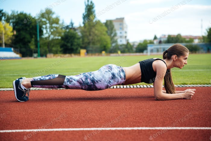 Woman athlete doing plank exercise on stadium
