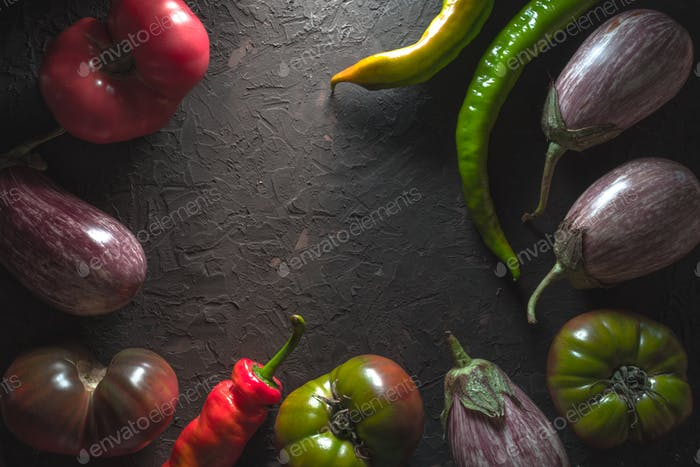 Frame of multi-colored tomatoes, aubergine and chili on a gray table