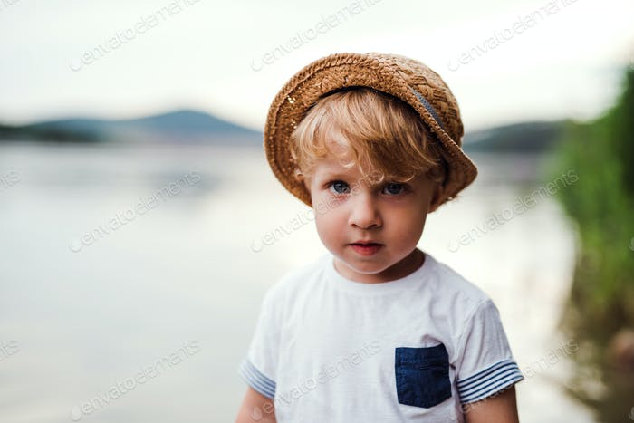 A small toddler boy standing outdoors by a river in summer, looking at camera.