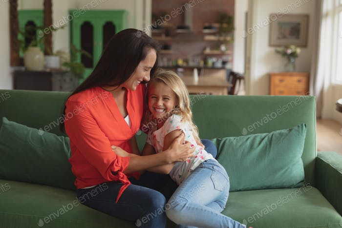 Front view of Caucasian mother and daughter having fun on a sofa living room at home